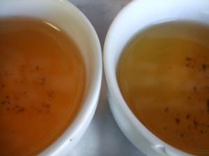 Two cups of Jasmine Pearl teas: the dark colors indicate more leaf than bud in the tea material.